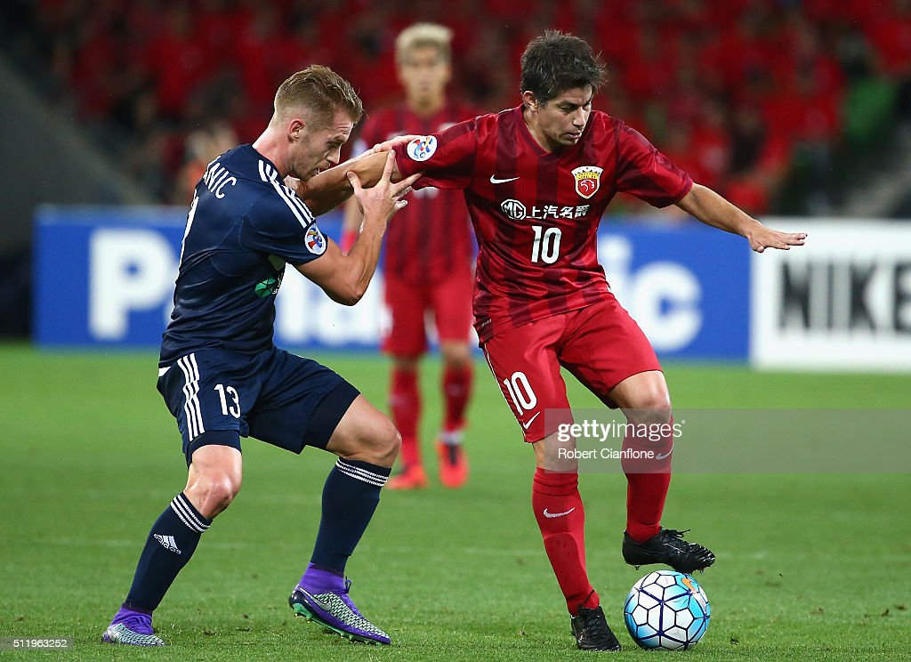 Dario Conca of Shanghai SIPG is challenged by Oliver Bozanic of Melbourne Victory during the AFC Asian Champions League match between Melbourne...