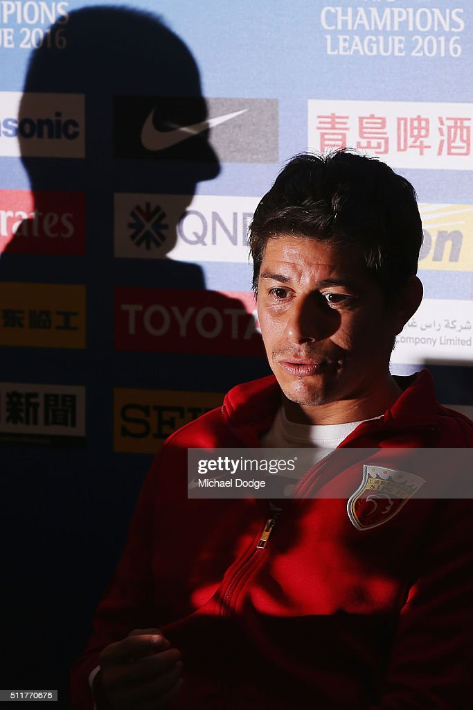 Dario Conca speaks to the media as the shadow of head coach Sven Goran Eriksson is seen next to him during a Shanghai SIPG Press Conference at AAMI...