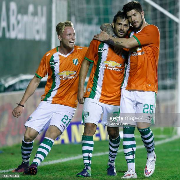 Dario Cvitanich of Banfield celebrates with teammates Carlos Matheu and Thomas Rodríguez after scoring the third goal of his team during a match...