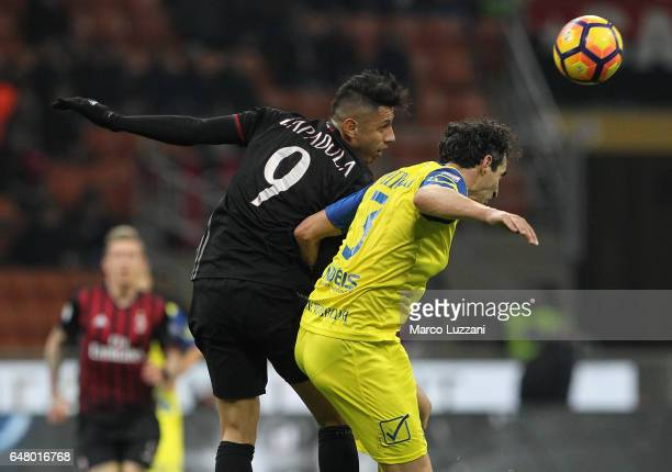 Dario Dainelli of AC Chievo Verona competes for the ball with Gianluca Lapadula of AC Milan during the Serie A match between AC Milan and AC...