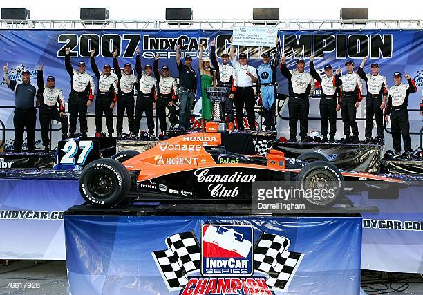 Dario Franchitti driver of the Andretti Green Racing Dallara Honda with the 2007 Championship Trophy and team members after winning the series and...