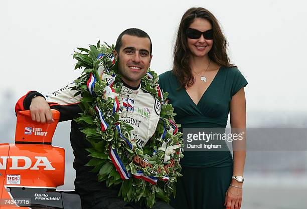 Dario Franchitti driver of the Canadian Club Andretti Green Racing Dallara Honda poses for a photo with his wife Ashley Judd during the Official Borg...
