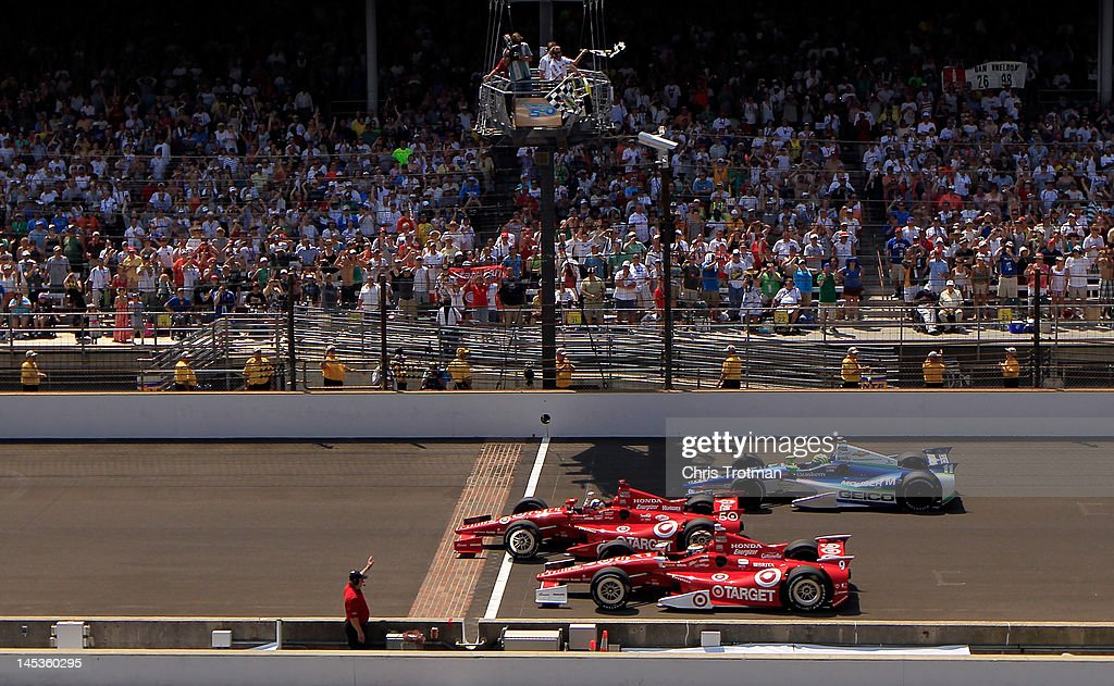 <a gi-track='captionPersonalityLinkClicked' href=/galleries/search?phrase=Dario+Franchitti&family=editorial&specificpeople=171306 ng-click='$event.stopPropagation()'>Dario Franchitti</a> of Scotland, driver of the #50 Target Chip Ganassi Racing Honda crosses the yard of bricks start/finish line to take the checkered flag ahead of teammate <a gi-track='captionPersonalityLinkClicked' href=/galleries/search?phrase=Scott+Dixon&family=editorial&specificpeople=183395 ng-click='$event.stopPropagation()'>Scott Dixon</a> (bottom) of New Zealand, driver of the #9 Target Chip Ganassi Racing Honda and Tony Kannan of Brazil, driver of the #11 GEICO-Mouser Electronics KVRT Chevrolet to give Franchitti the win in the IZOD IndyCar Series 96th running of the Indianapolis 500 mile race at the Indianapolis Motor Speedway on May 27, 2012 in Indianapolis, Indiana.