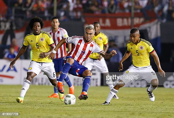 Dario Lezcano of Paraguay fights for the ball with Carlos Sanchez and Wilmar Barrios of Colombia during a match between Paraguay and Colombia as part...