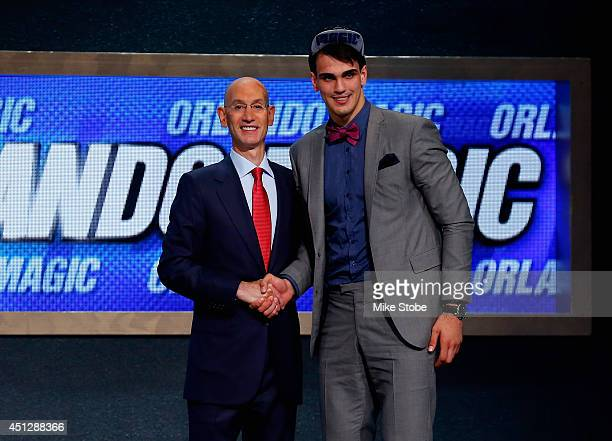 Dario Saric of Croatia shakes hands with NBA Commissioner Adam Silver after being drafted with the overall pick by the Orlando Magic during the 2014...