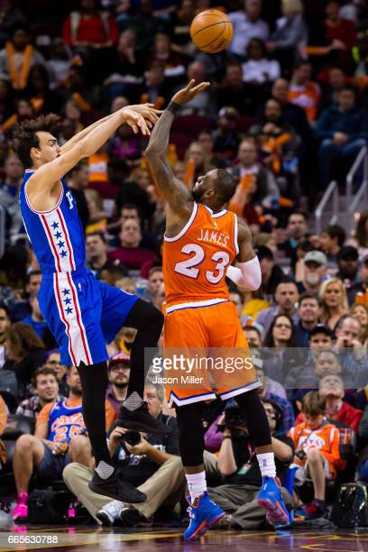 Dario Saric of the Philadelphia 76ers passes over LeBron James of the Cleveland Cavaliers during the second half at Quicken Loans Arena on March 31...