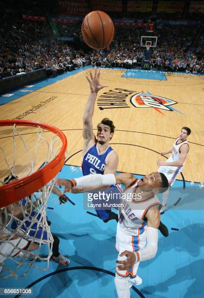 Dario Saric of the Philadelphia 76ers shoots the ball against Russell Westbrook of the Oklahoma City Thunder during the game on March 22 2017 at...