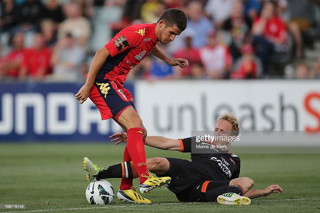 Dario Vidosic of Adelaide is tackled by Mitchell Nichols of Brisbane during the round 13 A-League match between Adelaide United and the Brisbane Roar at Hindmarsh Stadium on December 26, 2012 in Adelaide, Australia.