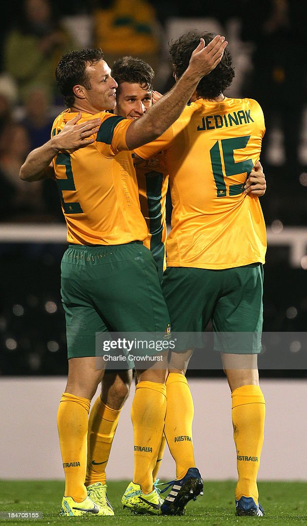 Dario Vidosic of Australia celebrates with team mates Lucas Neill and Mile Jedinak after scoring the teams second goal of the game during the International Friendly match between Canada and Australia at Craven Cottage on October 15, 2013 in London, England.