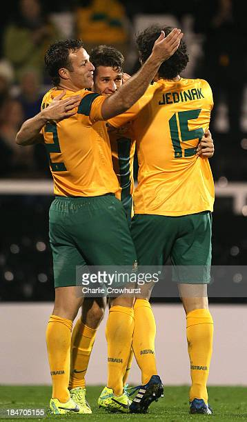 Dario Vidosic of Australia celebrates with team mates Lucas Neill and Mile Jedinak after scoring the teams second goal of the game during the...