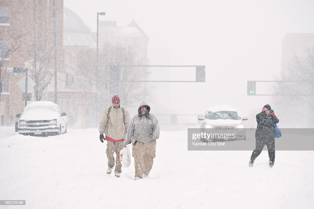 Darion Wilson, left, and Mari Alston, center, walk down the middle of Broadway Boulevard as the two Family Dollar employees walked home after the store closed early due to heavy snowfall that blanketed the metro area, Thursday, February 21, 2013.