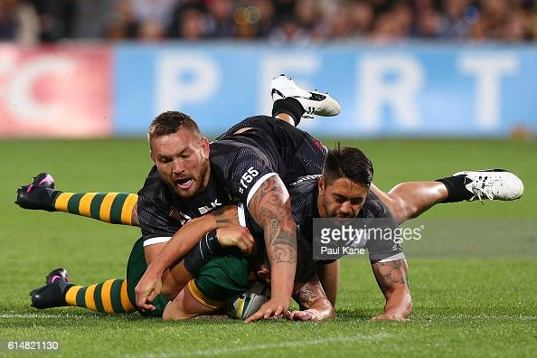Darius Boyd of Australia gets tackled by Jared WaereaHargreaves and Shaun Johnson of New Zealand during the International Rugby League Test match...