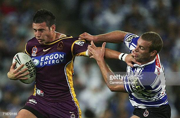 Darius Boyd of the Broncos is tackled by Daniel Holdsworth of the Bulldogs during the round 24 NRL match between the Bulldogs and the Brisbane...