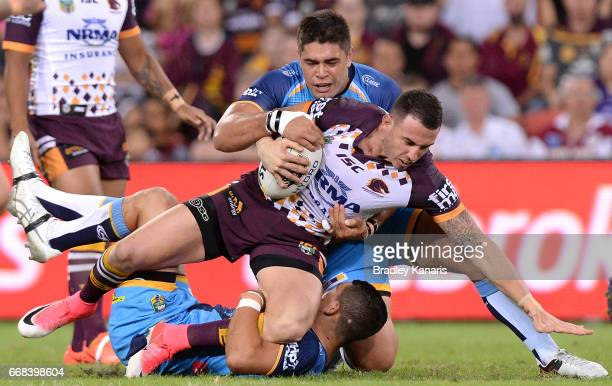 Darius Boyd of the Broncos is tackled during the round seven NRL match between the Brisbane Broncos and the Gold Coast Titans at Suncorp Stadium on...