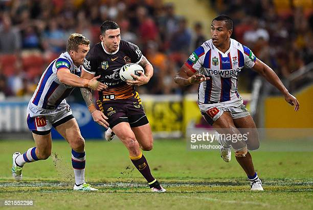 Darius Boyd of the Broncos makes a break past Trent Hodkinson and Jacob Saifiti of the Knights during the round seven NRL match between the Brisbane...
