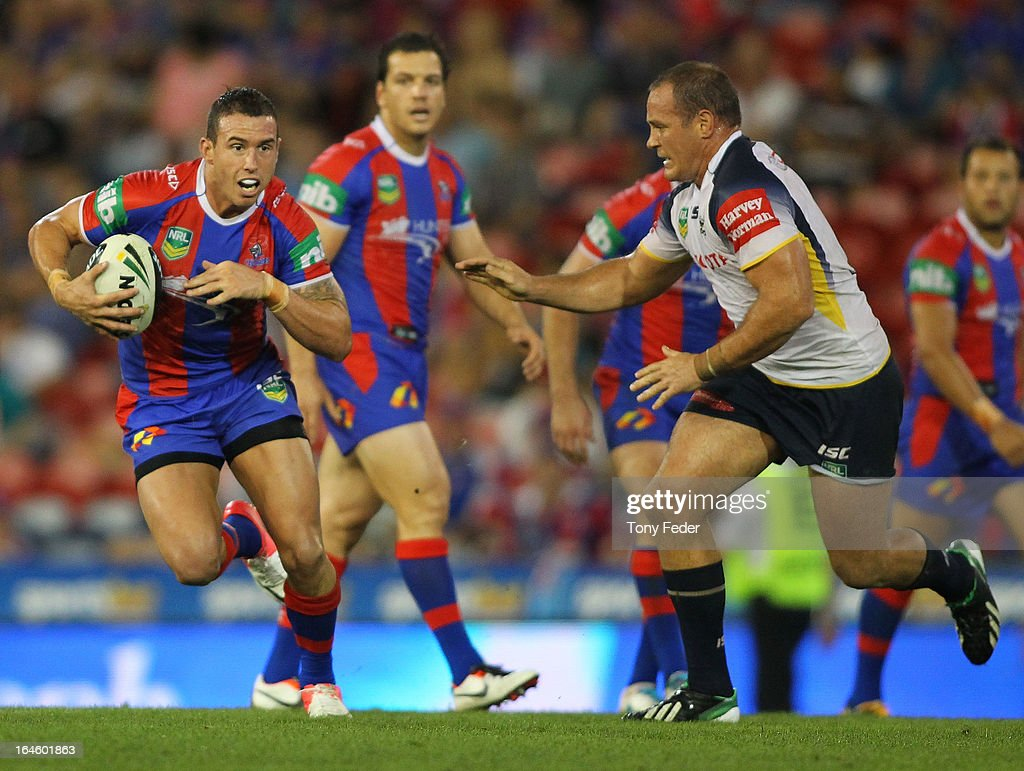 Darius Boyd of the Knights passes through Cowboys defence during the round three NRL match between the Newcastle Knights and the North Queensland Cowboys at Hunter Stadium on March 25, 2013 in Newcastle, Australia.