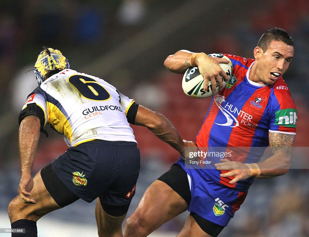 Darius Boyd of the Knights passes through Cowboys defender Johnathan Thurston during the round three NRL match between the Newcastle Knights and the North Queensland Cowboys at Hunter Stadium on March 25, 2013 in Newcastle, Australia.