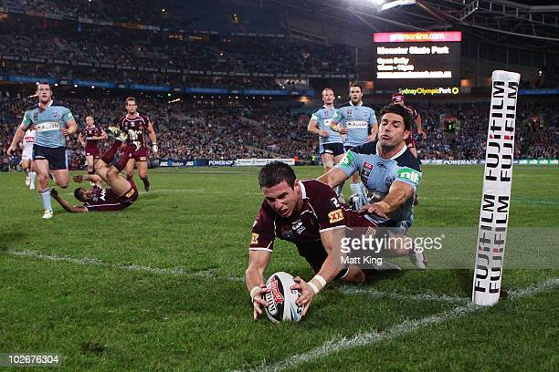 Darius Boyd of the Maroons beats the tackle of Trent Barrett of the Blues to score in the corner during game three of the ARL State of Origin series...