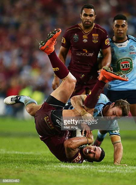 Darius Boyd of the Maroons is tackled by James Maloney of the Blues during game one of the State Of Origin series between the New South Wales Blues...