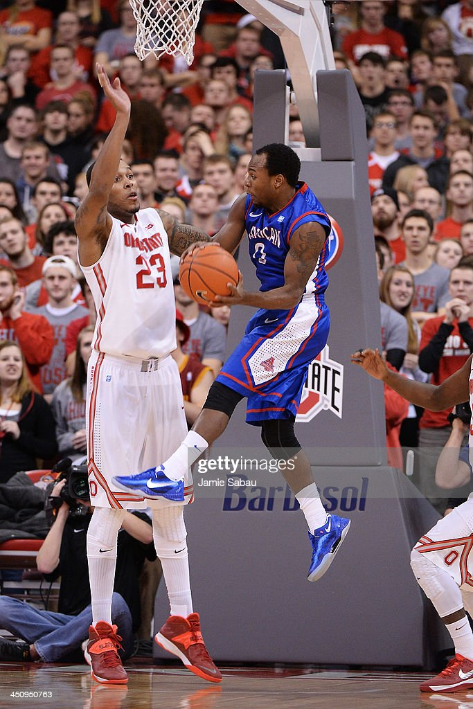 Darius Gardner #0 of the American University Eagles passes off the ball past the defense of Amir Williams #23 of the Ohio State Buckeyes in the second half on November 20, 2013 at Value City Arena in Columbus, Ohio. Ohio State defeated American 63-52.