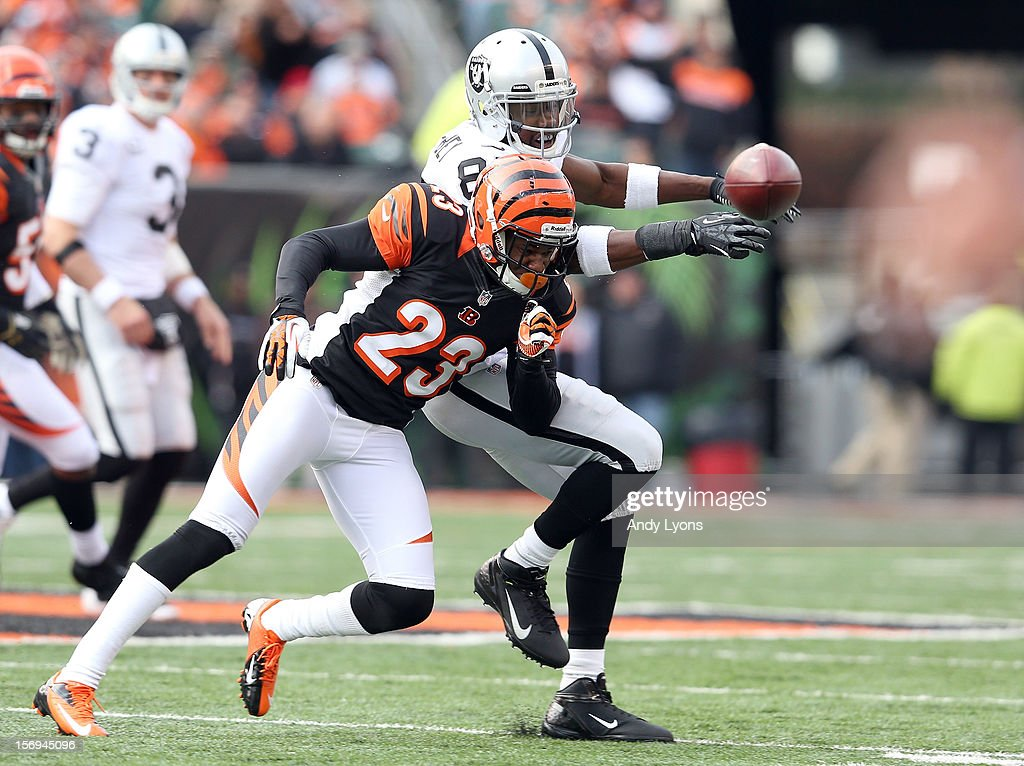 Darius Heyward-Bey #85 of the Oakland Raiders dropps the ball as he is hit by Terrence Newman #23 of the Cincinnati Bengals as he throws a pass during the NFL game at Paul Brown Stadium on November 25, 2012 in Cincinnati, Ohio.