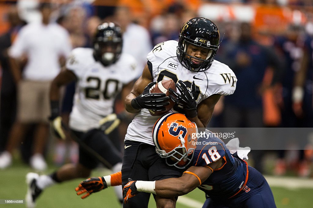 Darius Kelly #18 of Syracuse Orange wraps up Jonathan Williams #83 of Wake Forest Demon Deacons following a short first down reception in the fourth quarter on November 2, 2013 at the Carrier Dome in Syracuse, New York. Syracuse shuts out Wake Forest 13-0