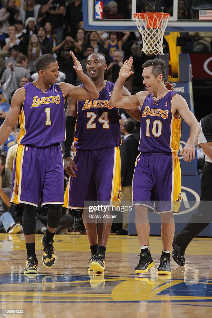 Darius Morris #1, Kobe Bryant #24, and Steve Nash #10 of the Los Angeles Lakers high five each other during a game against the Golden State Warriors on December 22, 2012 at Oracle Arena in Oakland, California.