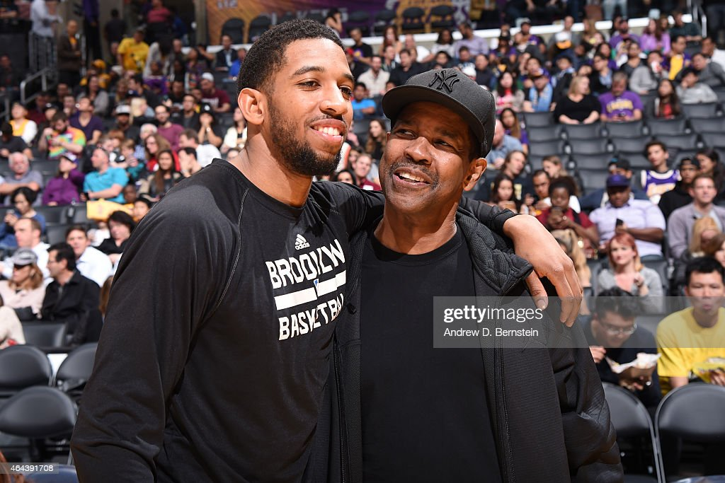 Darius Morris of the Brooklyn Nets and actor Denzel Washington speak before a game against the Los Angeles Lakers at STAPLES Center on February 20...