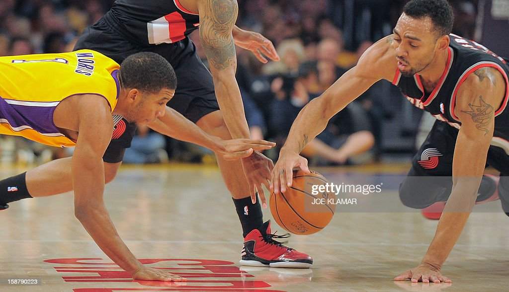 Darius Morris (L) of the Los Angeles Lakers and Jared Jeffries (R) of the Portland Trail Blazers scramble for a loose ball during their NBA game on December 28, 2012 at Staples Center in Los Angeles, California. AFP PHOTO / Joe KLAMAR