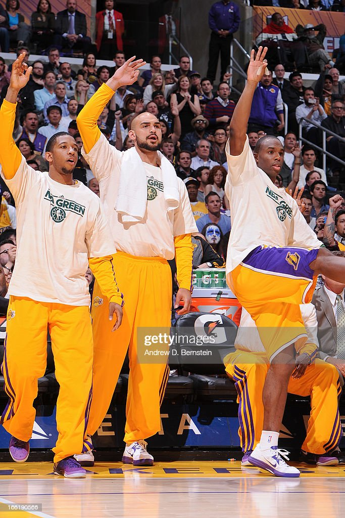Darius Morris #1, Robert Sacre #50, and Jodie Meeks #20 of the Los Angeles Lakers celebrate from the sideline during a game against the New Orleans Hornets at Staples Center on April 9, 2013 in Los Angeles, California.
