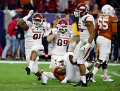 Darius Philon and Mitchell Loewen of Arkansas Razorbacks celebrate after sacking Tyrone Swoopes of the Texas Longhorns in the first half of their...