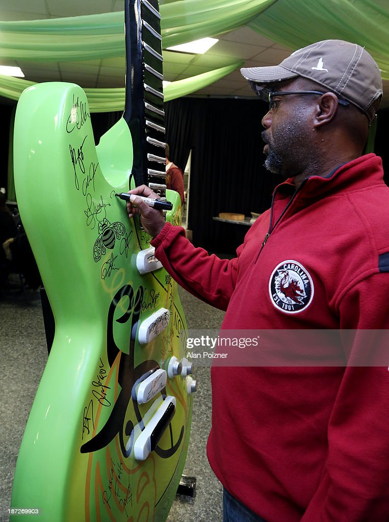 Darius Rucker signs a giant Patron tequila guitar backstage at the CMA Awards to benefit the 'Keep the Music Playing' music education on November 3, 2013 in Nashville, Tennessee.