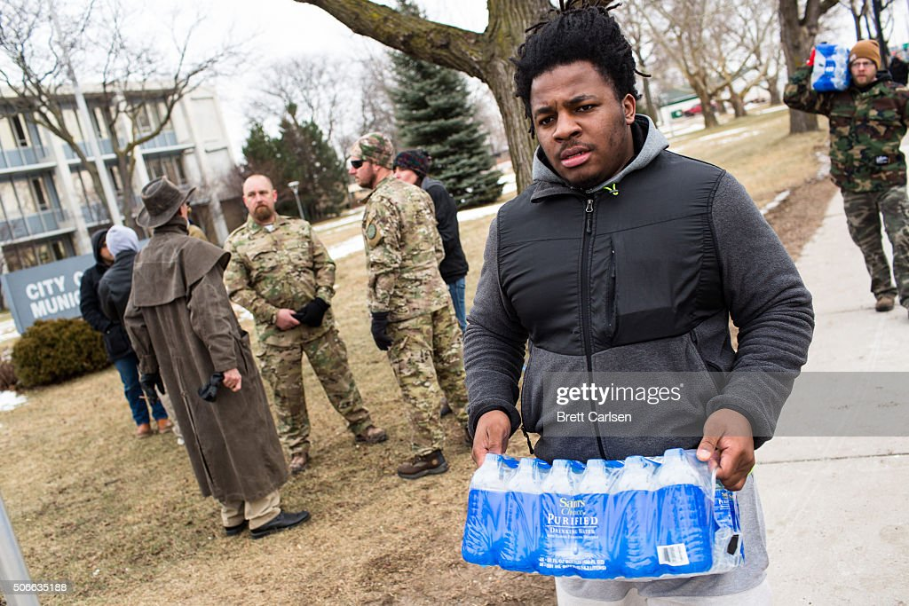 Darius Simpson an Eastern Michigan University student from Akron Ohio carries water he brought to donate for Flint residents during a rally on...