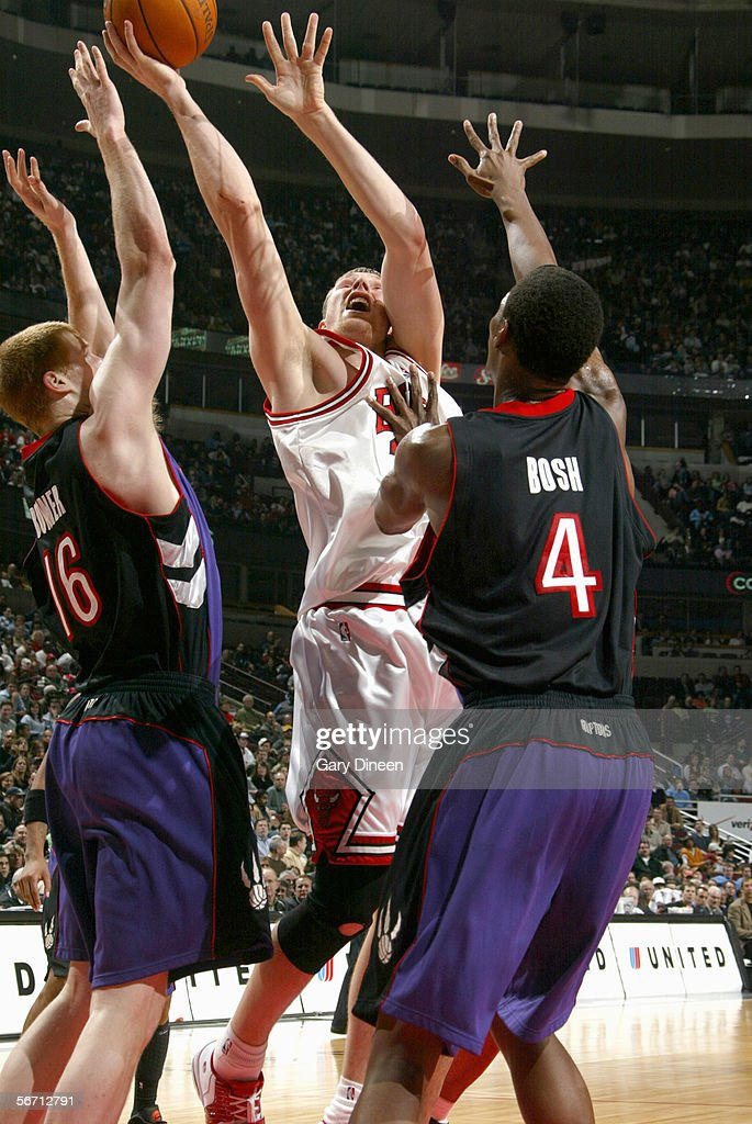 Darius Songaila #25 of the Chicago Bulls goes up for the ball against Matt Bonner #16 and Chris Bosh #4 of the Toronto Raptors during the game at the United Center on January 9, 2006 in Chicago, Illinois. The Bulls won 113-104.