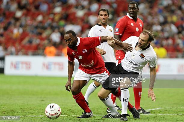 Darius Vassell of England and Jens Nowotny of Germany challenge for the ball during the Battle of Europe match between England Masters and Germany...