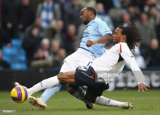 Darius Vassell of Manchester City is tackled by Ricardo Gardner of Bolton Wanderers during the Barclays Premier League match between Manchester City...