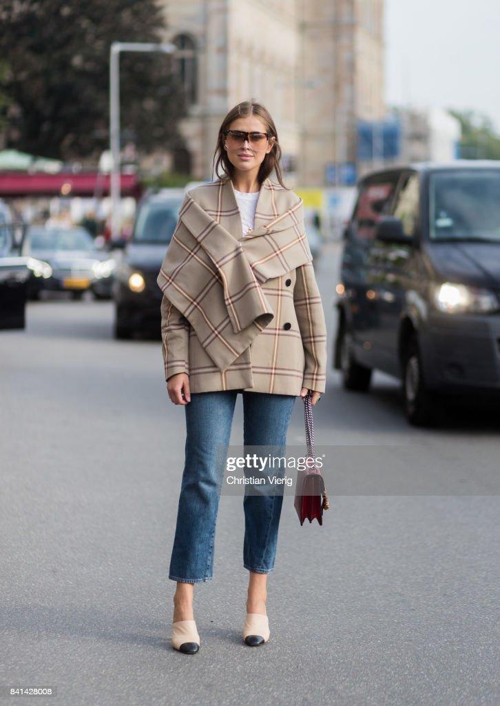 Darja Barannik wearing beige checked jacket, Chanel shoes, red Gucci bag, denim jeans outside House of Dagmar on August 31, 2017 in Stockholm, Sweden.