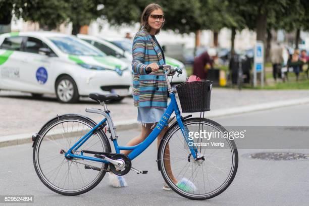 Darja Barannik with her bike wearing a denim skirt red Gucci skirt striped blazer outside Baum Und Pferdgarten on August 10 2017 in Copenhagen Denmark