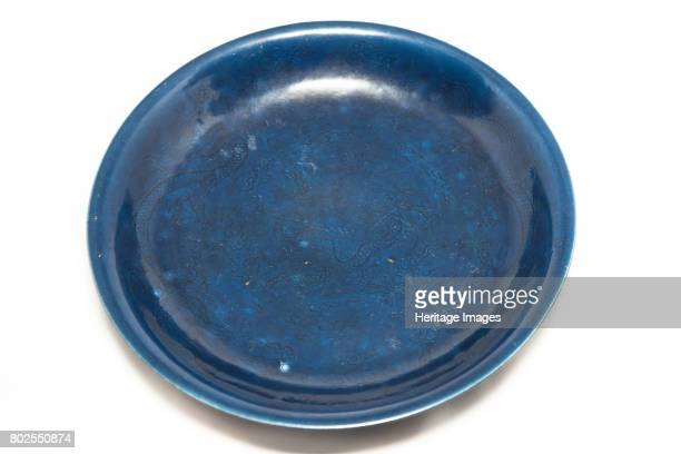 A dark blue monochrome deep dish with carved frontally facing imperial fiveclawed dragon design amid clouds in the centre chasing flaming pearl The...