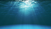 Dark blue ocean surface seen from underwater. Waves underwater and rays of sunlight shining through