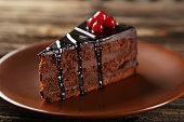 Dark chocolate cake on brown wooden background