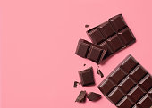 Dark chocolate on pink background. Top view