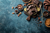 Dark chocolate pieces crushed and cocoa beans, culinary background, top view