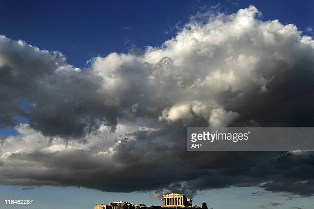 A dark cloud sits over the ancient temple of Parthenon atop the Acropolis hill illuminated by the late evening sun in Athens on May 18 2010 AFP PHOTO...