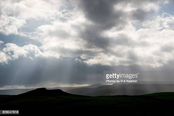Dark clouds and sunbeams over Northern hills