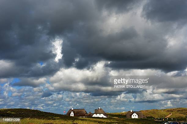 Dark clouds hang over thatched houses in Kampen on the German North Sea island of Sylt nothern Germany on July 30 2012 Meteorologists forecast...