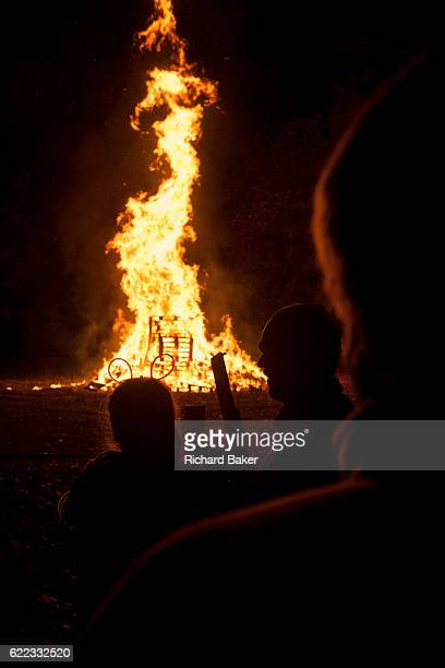 Dark figures stand in silence to watch the crackling flames of a bonfire during the annual bonfire night on 5th November 2016 in Kington...