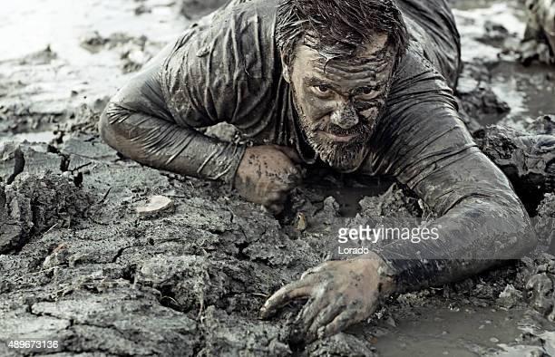 À poil noir homme ramper pendant une course dans la boue