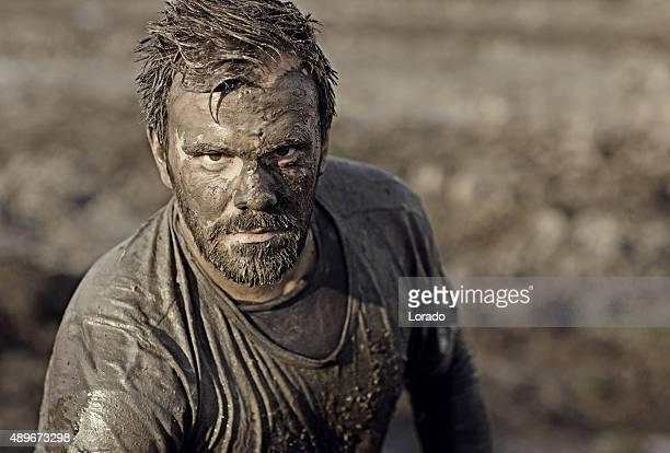 Dunkle langhaarigem Mann posieren für ein mud run