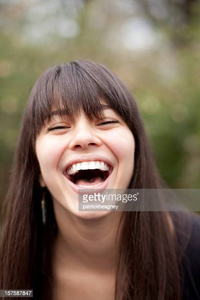 Dark haired woman with bangs is laughing
